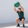 A guy doing glute exercise with a ball.